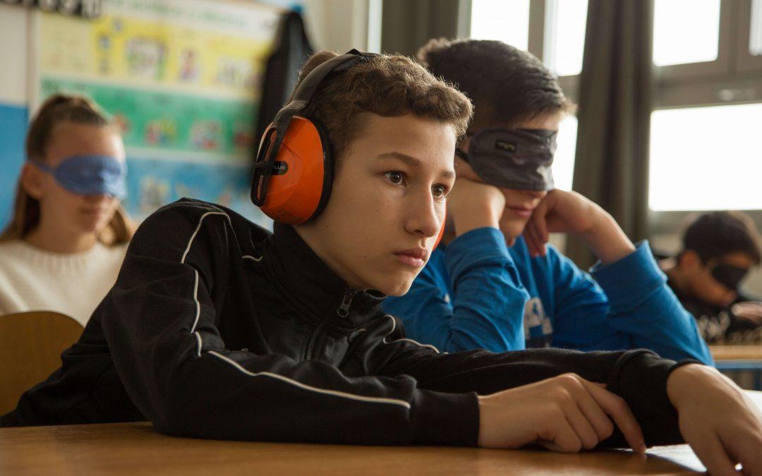 fotografija dvojice dječajka s gluhim slušalicama i povezom preko očiju